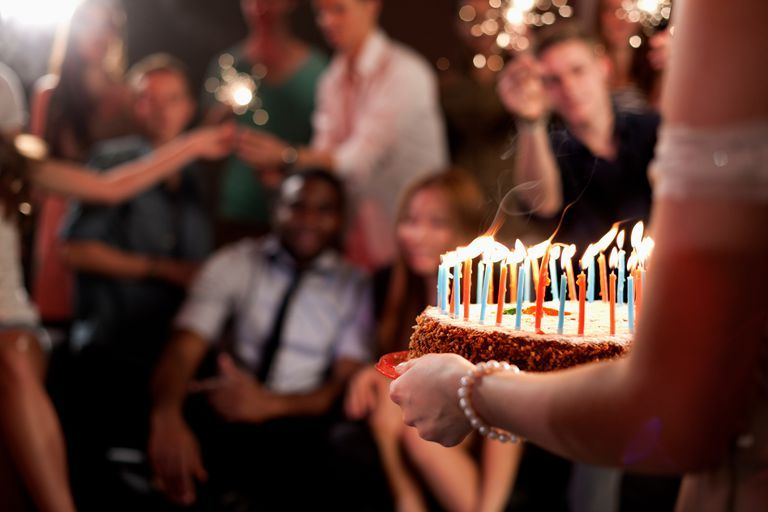 Person carrying birthday cake group of friends in background