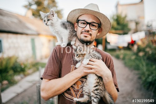Happpy young bearded farmer holding two little kitten in hands outdoor in village with abstract background