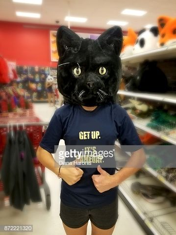 A Girl Is Standing In A Store Wearing A Funny Black Cat Mask Stock