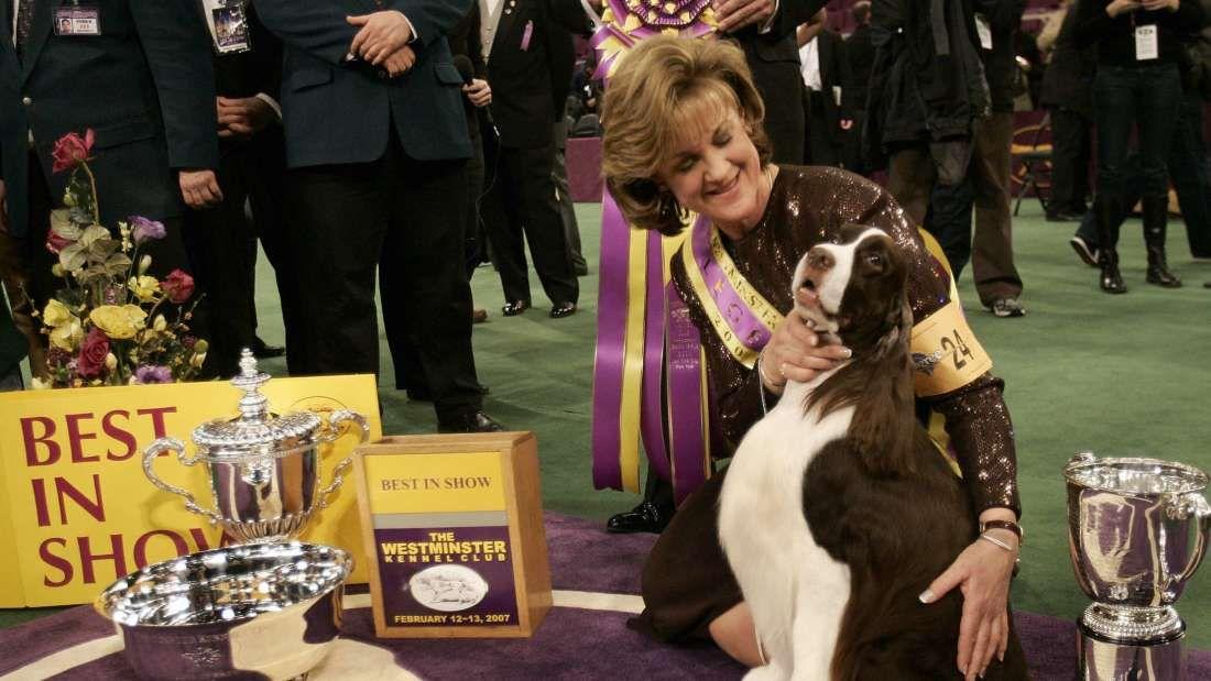Dog handler Kellie Fitzgerald poses with her English Springer Spaniel James after winning Best