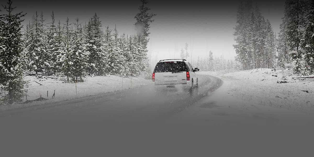 of an SUV driving on a road during a snowstorm