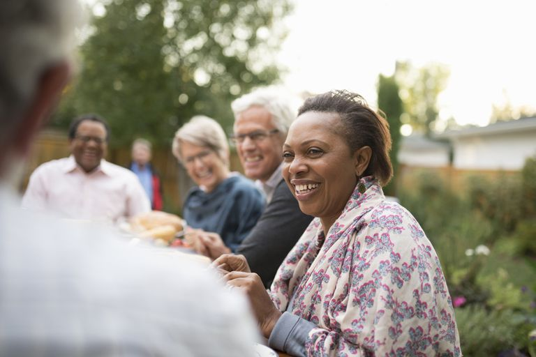 Smiling senior woman enjoying garden party lunch with friends on patio