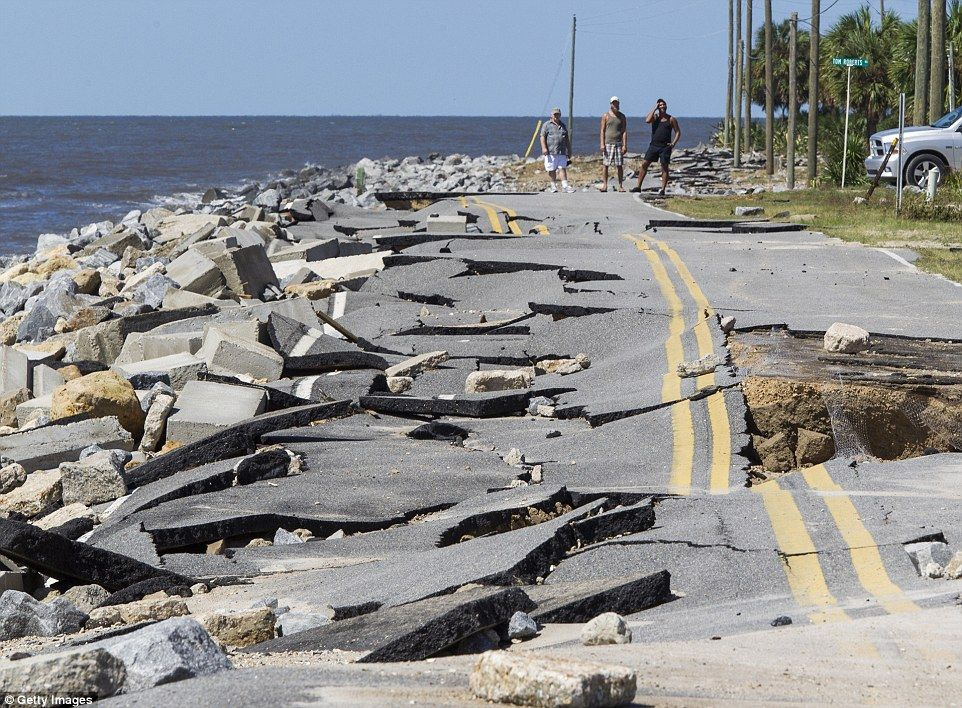 Residents in Alligator Point Florida look at a road that collapsed during the storm surge